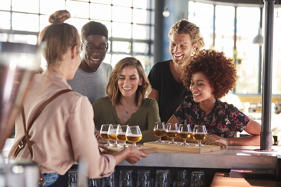 Specialized Business Insurance - Waitress Serving a Happy Group Of Friends Beer Tasting In a Local Brewery